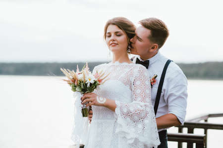 Photo pour Happy newly married couple, smiling bride brunette young woman with boho style bouquet with groom, outdoors - image libre de droit