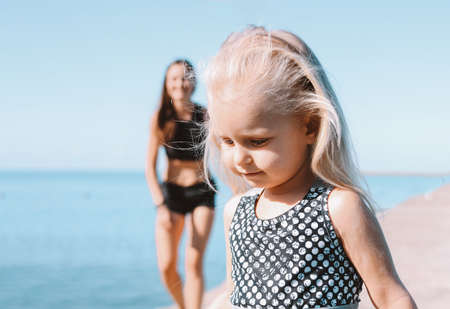 Photo pour Little cute girl running to fit mom on the beach, healthy lifestyle, sport family - image libre de droit