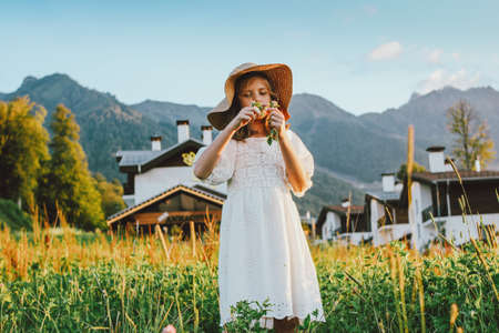 Photo pour Beautiful romantic preteen girl in straw hat picking flowers against the background of beautiful houses in the mountain, rural scene at sunset - image libre de droit