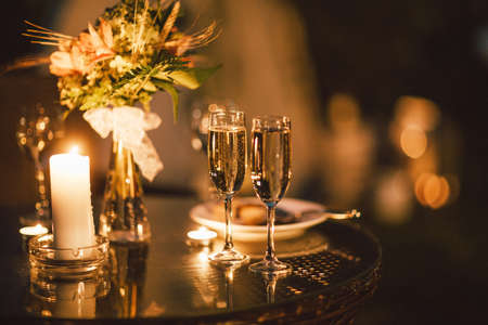 Photo for Two glasses of wine on table on the background of wedding bouquet, evening, the end of event - Royalty Free Image