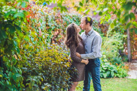 A pregnant young woman and her husband. A happy family standing at the red autumn hedge, holding belly. pregnant woman relaxing in the park. Lovely prospective mother