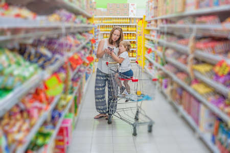 mother and her son buying food at a supermarket. shopping concept