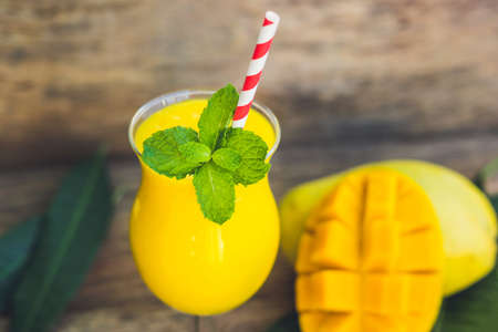 Juicy smoothie from mango in glass with striped red straw and with a mint leaf on old wooden background. Healthy life concept, copy space.