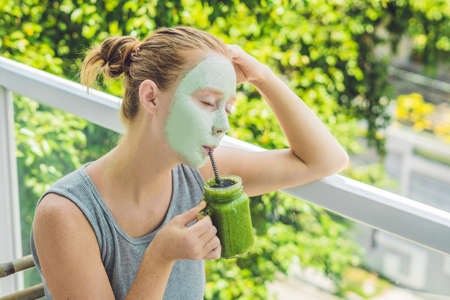 Spa Woman applying Facial green clay Mask. Beauty Treatments. Fresh green smoothie with banana and spinach with heart of sesame seeds. Love for a healthy raw food concept. Detox Concept.の写真素材