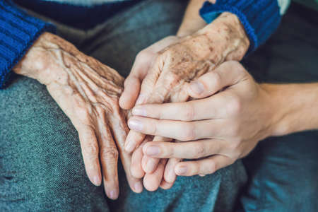 Foto de Hands of an old woman and a young man. Caring for the elderly. close up. - Imagen libre de derechos