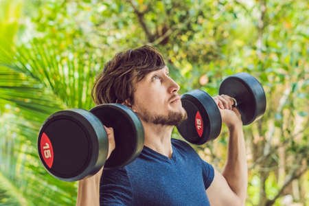 Training fitness man outside working out arms lifting dumbbells doing biceps curls. Male sports model exercising outdoors as part of healthy lifestyle.
