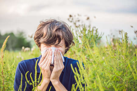 Photo pour Young man sneezes because of an allergy to ragweed. - image libre de droit