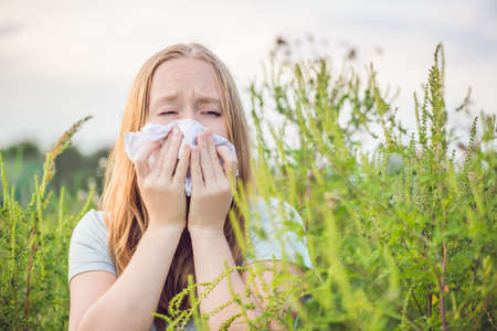 Photo pour Young woman sneezes because of an allergy to ragweed. - image libre de droit