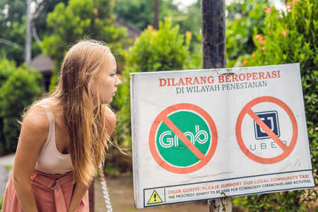 Young woman looks at protest sign on a wall in Indonesian objecting to Uber and Grab taxi drivers reads 'Uber and Grab Taxis No Entry' in Ubud, Bali, Indonesia.