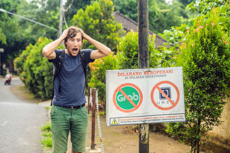Young man looks at protest sign on a wall in Indonesian objecting to Uber and Grab taxi drivers reads 'Uber and Grab Taxis No Entry' in Ubud, Bali, Indonesia.