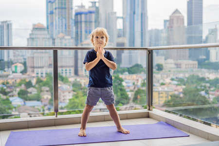 Happy little boy is practicing yoga on his balcony with a panoramic view of the big city.