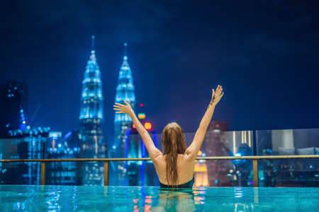 Photo for Young woman in outdoor swimming pool with city view at night. - Royalty Free Image