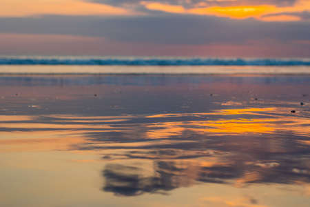 Sunset on the Kuta beach with reflection in the water on the island of Bali.