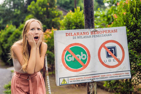 BALI, INDONESIA - 21 May, 2018: Young woman looks at protest sign on a wall in Indonesian objecting to Uber and Grab taxi drivers reads Uber and Grab Taxis No Entry in Ubud, Bali, Indonesia