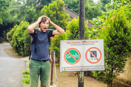 BALI, INDONESIA - 21 May, 2018: Young man looks at protest sign on a wall in Indonesian objecting to Uber and Grab taxi drivers reads Uber and Grab Taxis No Entry in Ubud, Bali, Indonesia