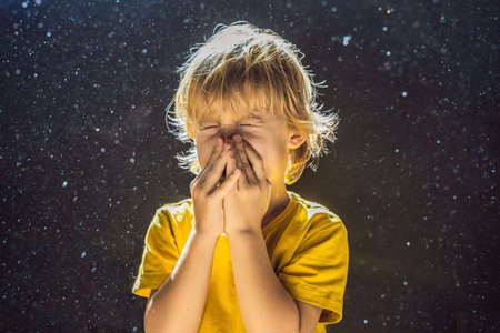 Photo pour Allergy to dust. Boy sneezes because he is allergic to dust. Dust flies in the air backlit by light - image libre de droit