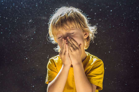 Photo for Allergy to dust. Boy sneezes because he is allergic to dust. Dust flies in the air backlit by light - Royalty Free Image