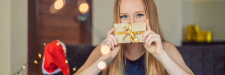 Young woman is packing presents. Present wrapped in craft paper with a red and gold ribbon for christmas or new year. Woman makes an advent calendar for her child.