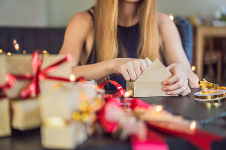 Young woman is packing presents. Present wrapped in craft paper with a red and gold ribbon for christmas, birthday, mother\'s day or valentine.