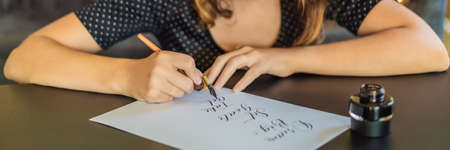 Calligrapher Young Woman writes phrase on white paper. Dream big, set goal, take an action. Inscribing ornamental decorated letters. Calligraphy, graphic design, lettering, handwriting, creation concept BANNER, LONG FORMAT