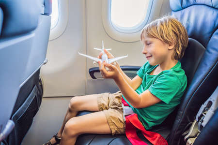Photo for Little boy play with toy plane in the commercial jet airplane flying on vacation - Royalty Free Image
