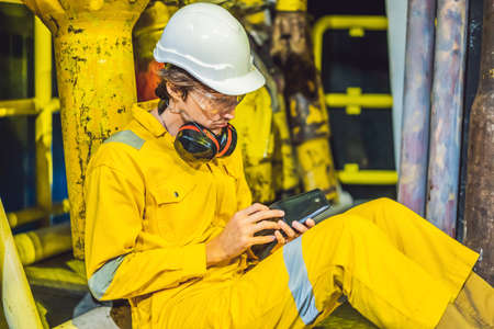 Young man in a yellow work uniform, glasses and helmet in industrial environment,oil Platform or liquefied gas plant looking into his empty wallet. Do not pay salary