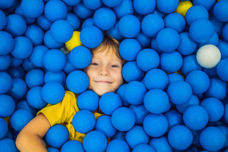 Foto de Child playing in ball pit. Colorful toys for kids. Kindergarten or preschool play room. Toddler kid at day care indoor playground. Balls pool for children. Birthday party for active preschooler - Imagen libre de derechos