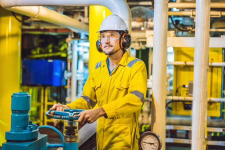 Photo pour Young man in a yellow work uniform, glasses and helmet in industrial environment,oil Platform or liquefied gas plant - image libre de droit