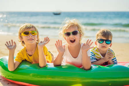 Photo pour Children sit on an inflatable mattress in sunglasses against the sea and have fun - image libre de droit