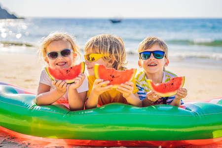 Photo pour Children eat watermelon on the beach in sunglasses - image libre de droit