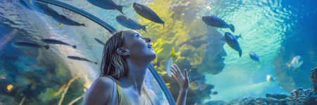 Foto de Young woman touches a stingray fish in an oceanarium tunnel BANNER, LONG FORMAT - Imagen libre de derechos