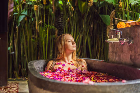Foto de Attractive Young woman in bath with petals of tropical flowers and aroma oils. Spa treatments for skin rejuvenation. Alluring woman in Spa salon. Girl relaxing in bathtub with flower petals. Luxury - Imagen libre de derechos