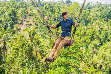 Photo for Young man swinging in the jungle rainforest of Bali island, Indonesia. Swing in the tropics. Swings - trend of Bali - Royalty Free Image