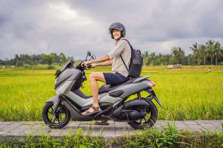 Photo for Male traveler on a bike among a rice field. Tourist travels to Bali - Royalty Free Image