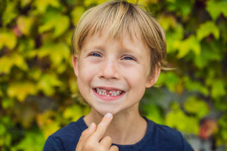 Photo for Little smiling child boy hand pointing his first   tooth fall out - Royalty Free Image