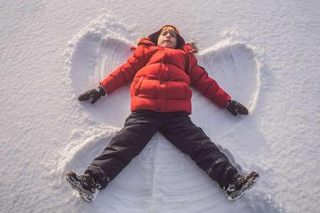 Foto de A child, a boy, lies on the snow - Imagen libre de derechos