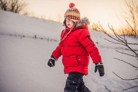 Foto de Cute boy in red winter clothes runs fun in the snow - Imagen libre de derechos