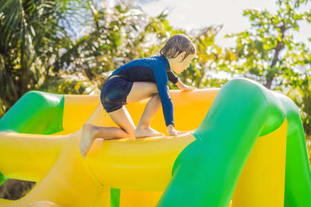 Photo for Cute boy runs an inflatable obstacle course in the pool. - Royalty Free Image