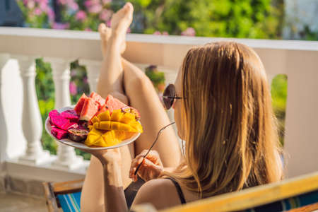 Photo pour Young woman resting on a balcony with a plate of fruit. life-work balance, relaxation healthy quality living lifestyle in summer holiday vacation of freelancer woman take it easy resting in resort hotel balcony having peace of mind - image libre de droit
