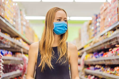 Photo pour Alarmed female wears medical mask against coronavirus while grocery shopping in supermarket or store- health, safety and pandemic concept - young woman wearing protective mask and stockpiling food - image libre de droit