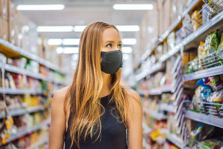 Foto für Alarmed female wears medical mask against coronavirus while grocery shopping in supermarket or store- health, safety and pandemic concept - young woman wearing protective mask and stockpiling food - Lizenzfreies Bild