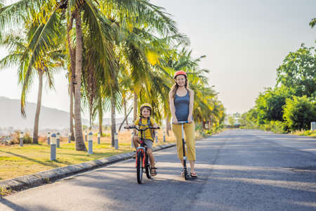 Active school kid boy and his mom in safety helmet riding a bike with backpack on sunny day. Happy child biking on way to school. Safe way for kids outdoors to school.
