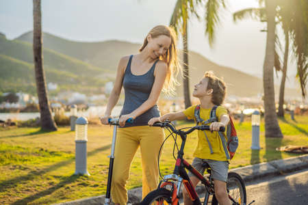 Photo pour Active school kid boy and his mom riding a bike with backpack on sunny day. Happy child biking on way to school. Safe way for kids outdoors to school - image libre de droit