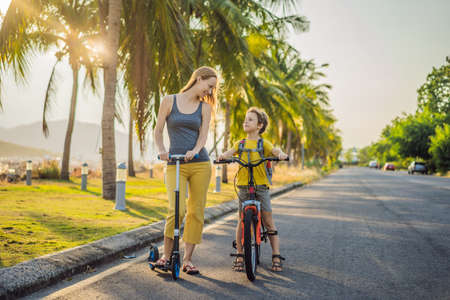 Active school kid boy and his mom riding a bike with backpack on sunny day. Happy child biking on way to school. Safe way for kids outdoors to school