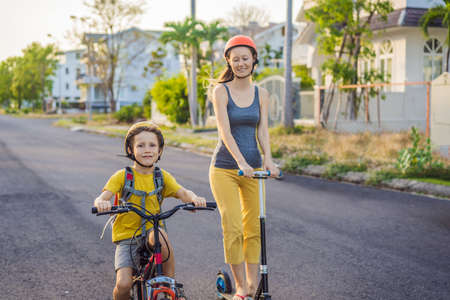 Active school kid boy and his mom in safety helmet riding a bike with backpack on sunny day. Happy child biking on way to school. Safe way for kids outdoors to school