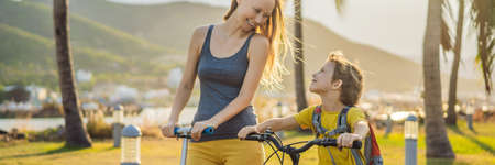 Active school kid boy and his mom riding a bike with backpack on sunny day. Happy child biking on way to school. Safe way for kids outdoors to school BANNER, LONG FORMAT