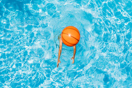 Photo for Man play in the pool with a beach ball - Royalty Free Image
