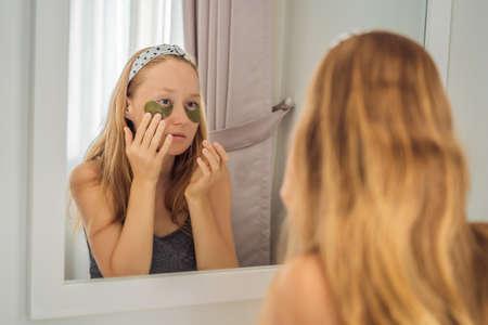 Photo pour Mirror reflection smiling woman applying hydrogel eye care patches, moisturizing skin under eyes, enjoying skincare procedures - image libre de droit