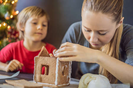 Photo for Young mother and kid making gingerbread house on Christmas eve - Royalty Free Image