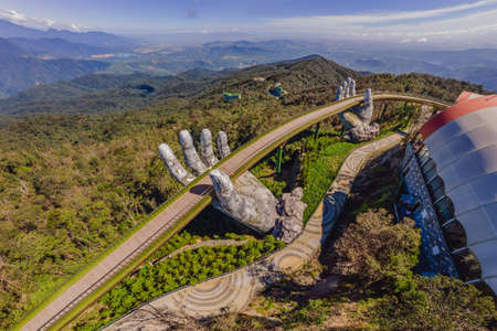 Photo pour Top aerial view of the famous Golden Bridge is lifted by two giant hands in the tourist resort on Ba Na Hill in Da Nang, Vietnam - image libre de droit